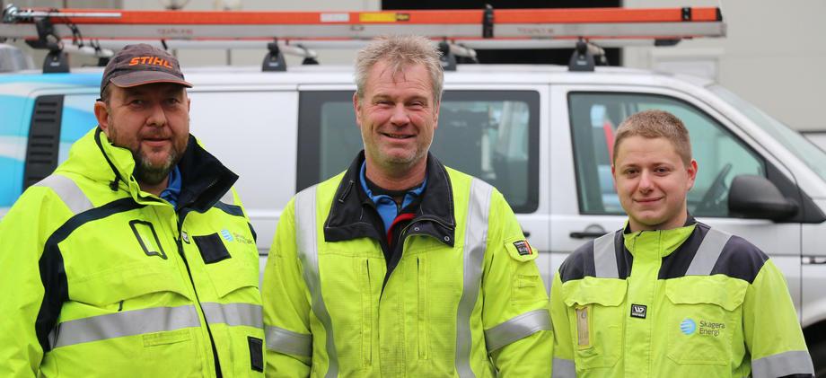 Rønningen, Christoffersen og Fjeldheim i arbeidstøy foran montørbil.