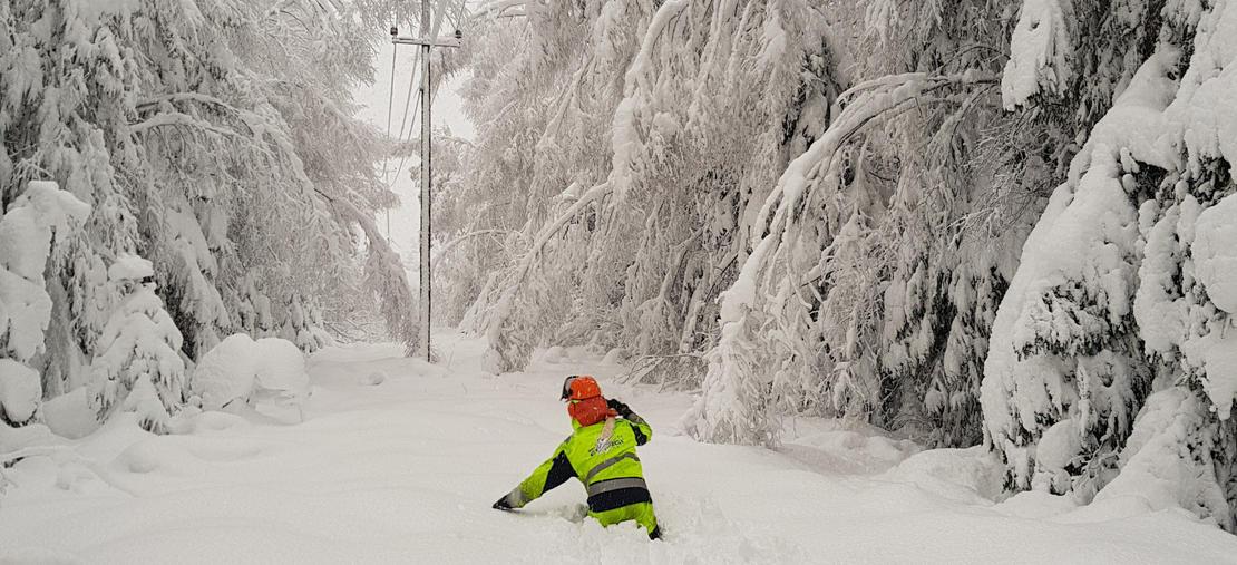 Montør i dyp snø under ledning