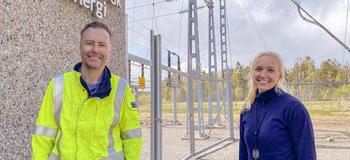 Mann og dame i arbeidsklær ved elektrisk høyspentanlegg.